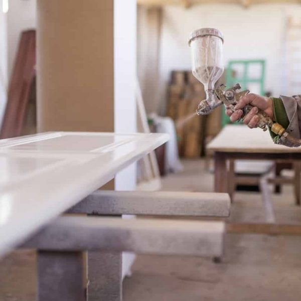 Close-up of spray gun getting paint over timber. Young painter renovating , Woman  painting wooden timber with spray paint gun. Female painting furniture details. Worker using spray gun. The carpenter paints furniture details in white color in the carpentry shop.